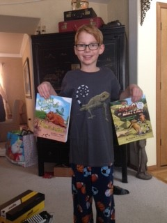 A boy stands holding his favorite curly-tail books by Elaine A. Powers.