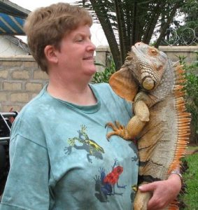 Elaine Powers stands holding green iguana, Eddie.