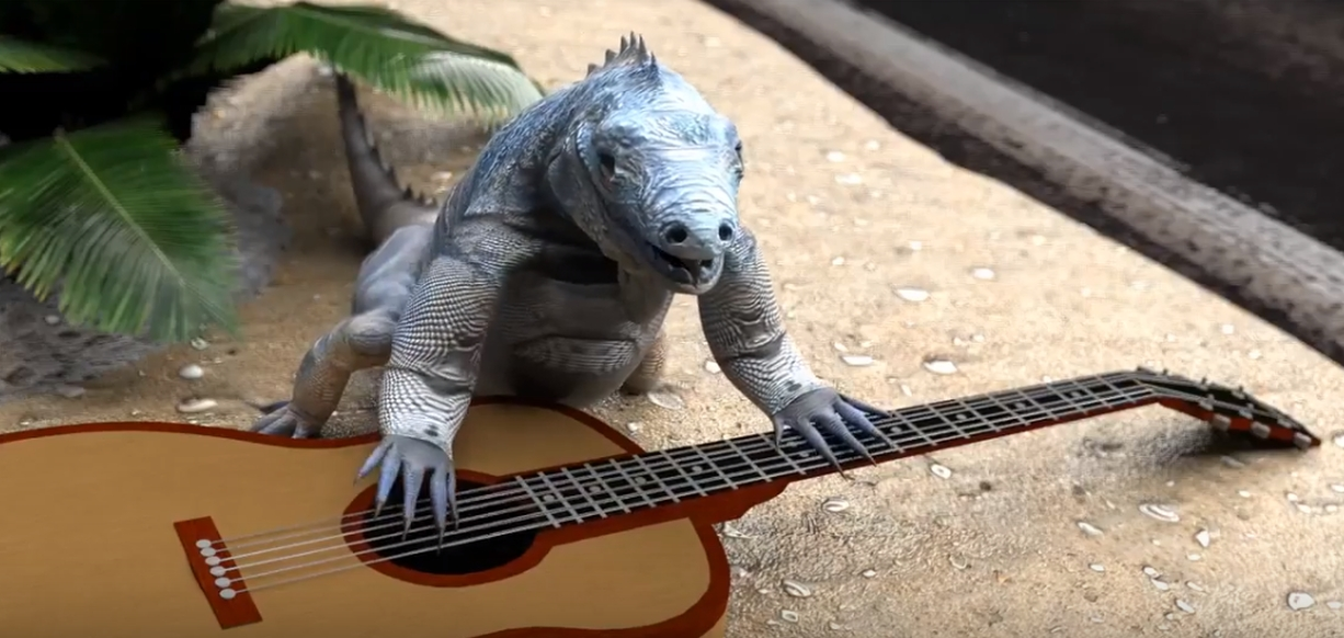 A rock iguana with a guitar, singing, on a sidewalk, near the road