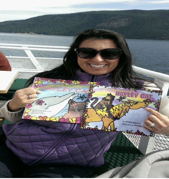A woman on a boat, holding up a children's book