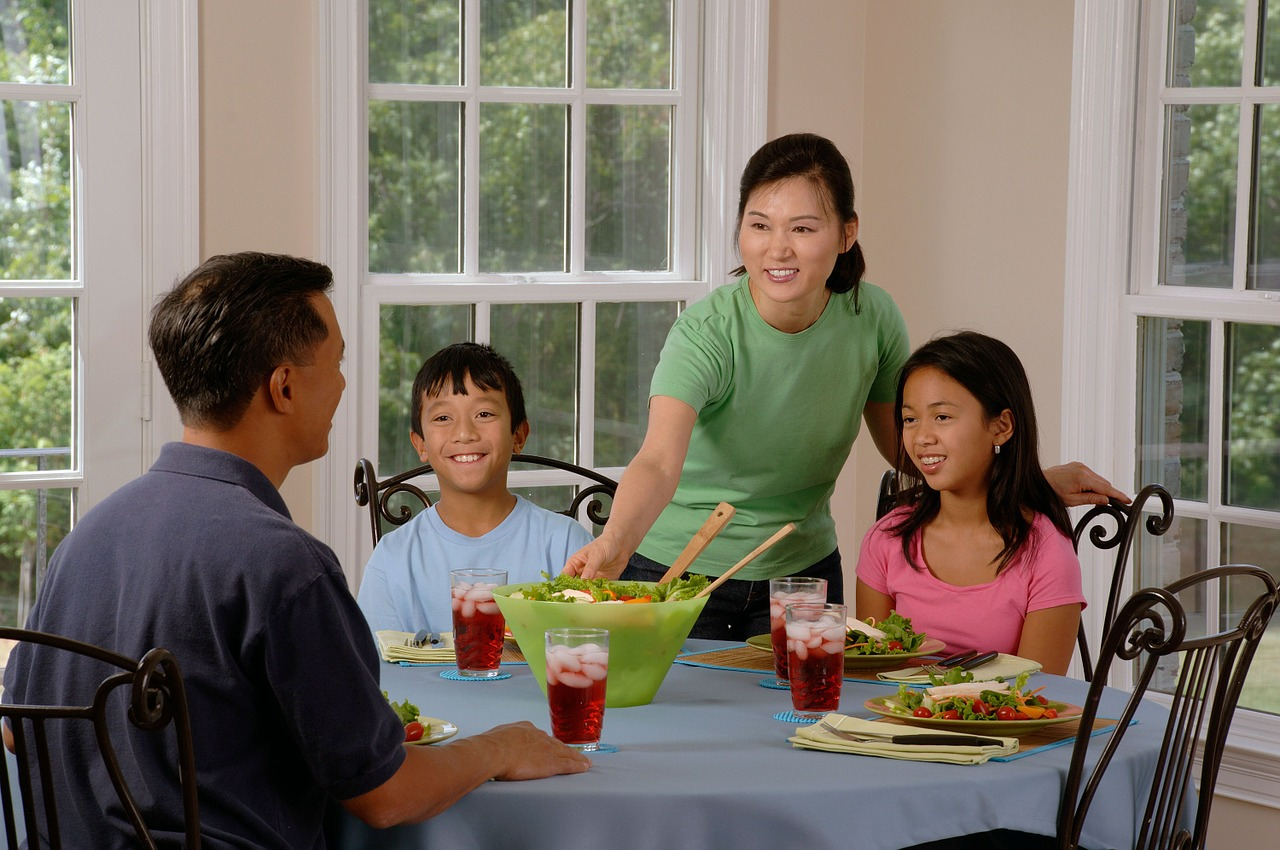 A father, mother and two children at the dinner table in a room with French doors and windows. Mother is placing a dish on the table.
