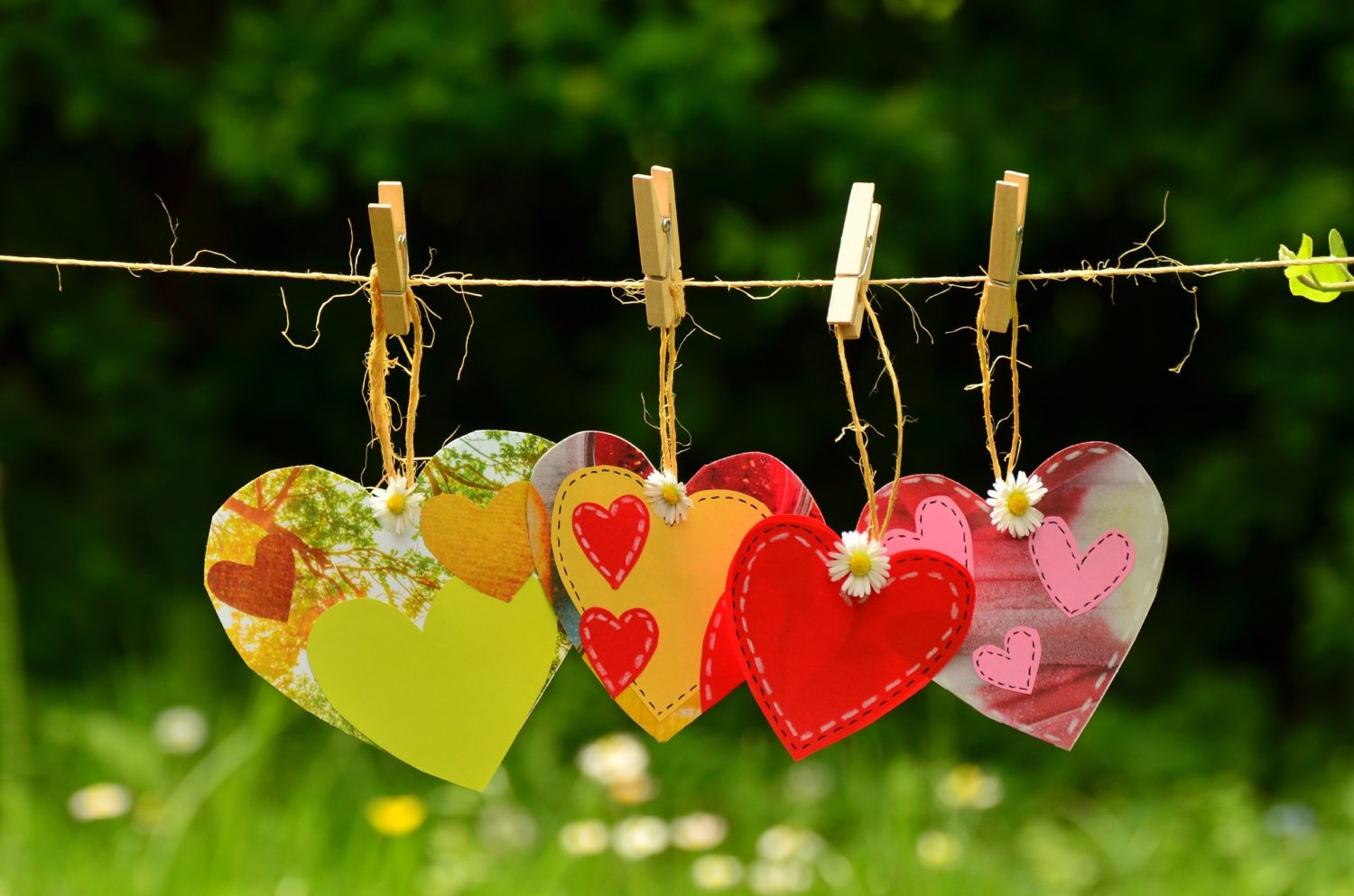 colorful paper hearts, red, yellow, pink, hanging from a clothesline by clothes pins, with a green bush and floral background