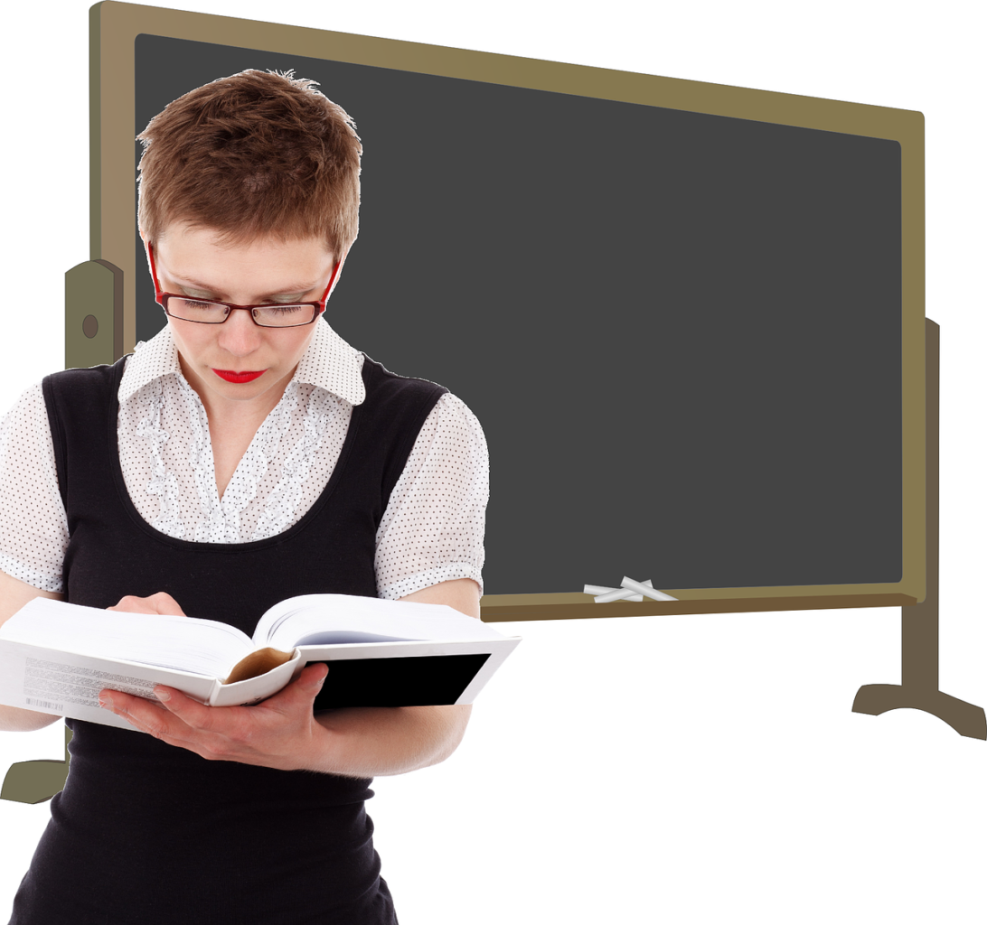 An illustration of a gray chalkboard, with an attractive woman about 30 with short red hair and glasses holding open a book to check something.