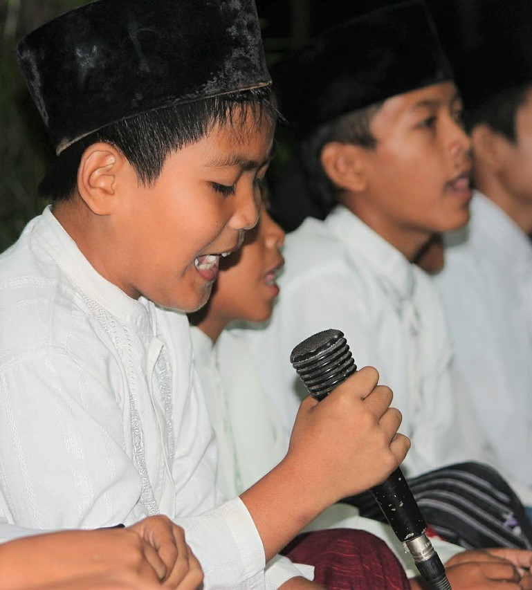 Boys dressed in white shirts sitting in a row. One boy holds a microphone and speaks into it