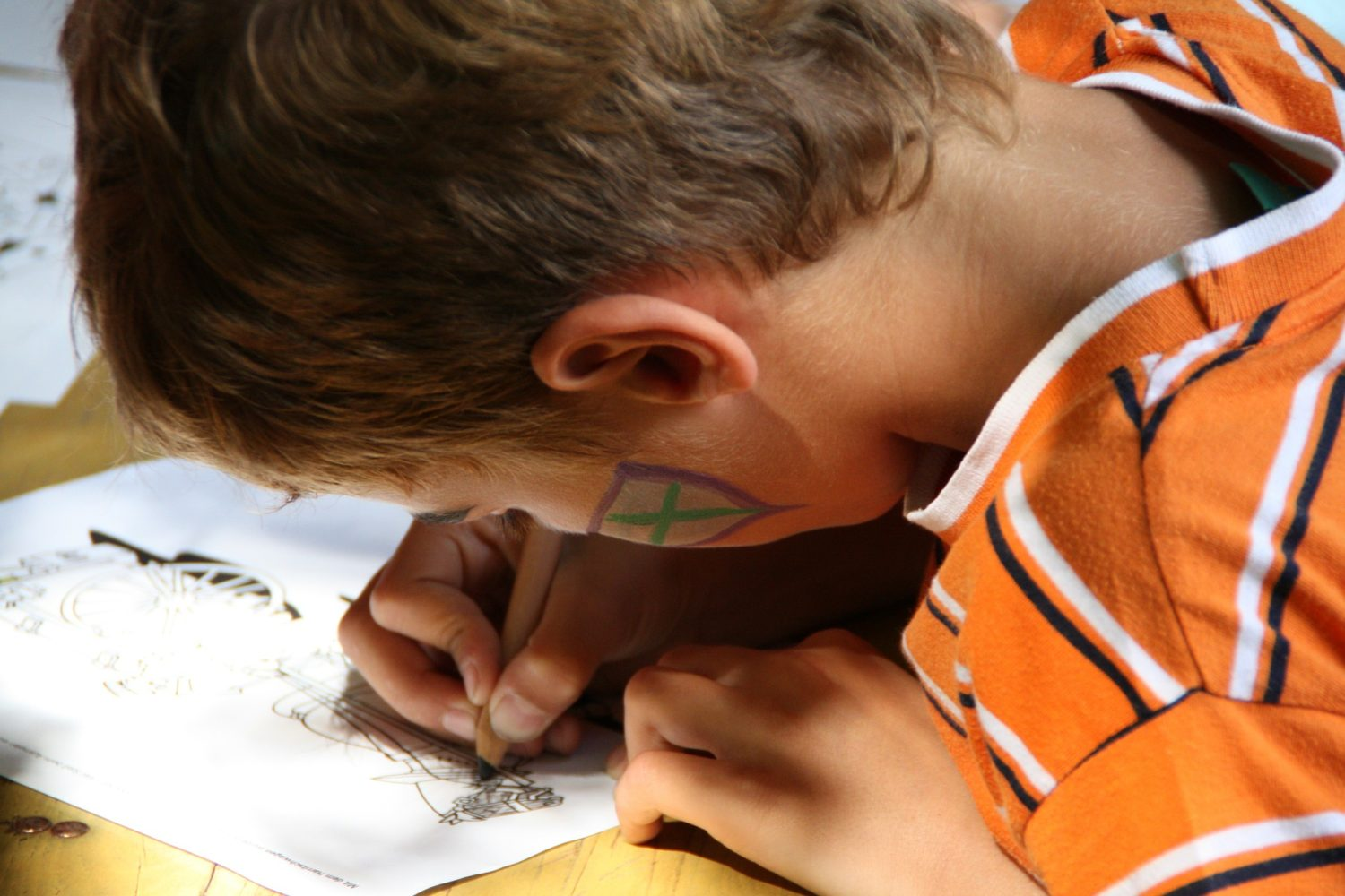 Close up of side of head and hands of child drawing on a piece of paper on top of a school desk