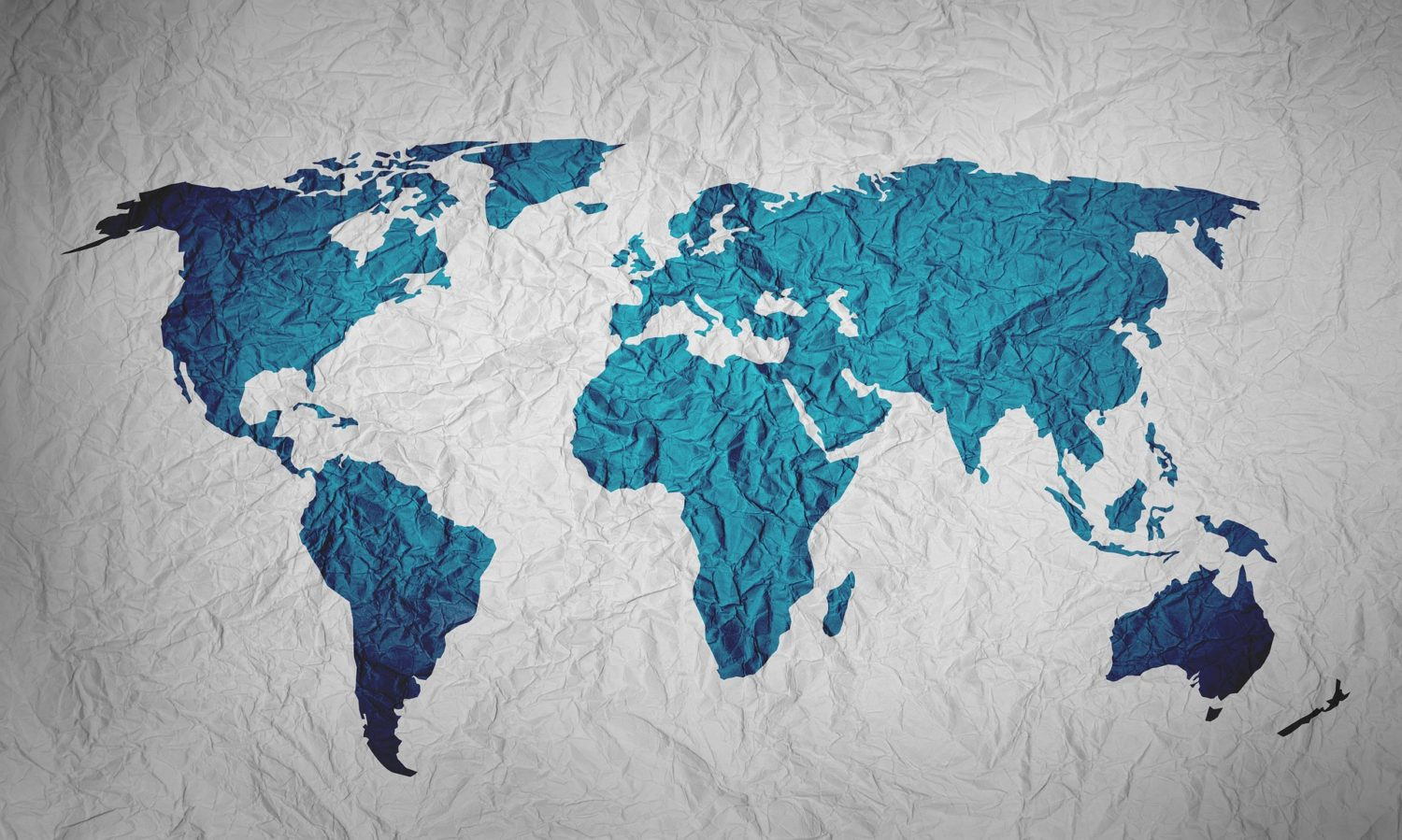 White crinkled paper with the world's continents drawn in turquoise blue ink
