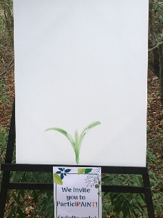 A white canvas on an easel, with a small three-leafed plant painted at the bottom