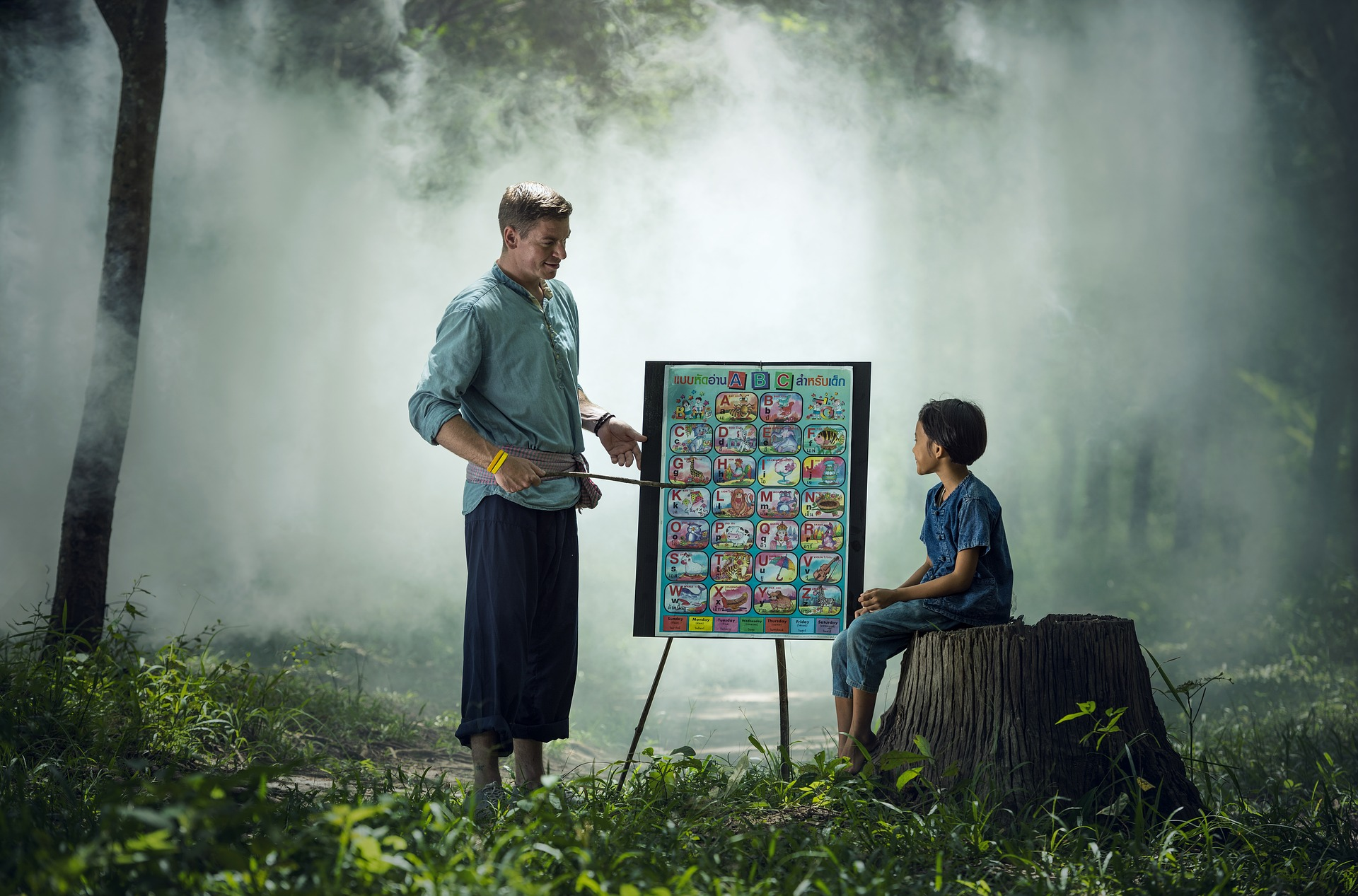 Setting: Forest, misty background. A man stands at white board with pointer stick. A child sits on tree trucnk looking at drawings on whiteboard.