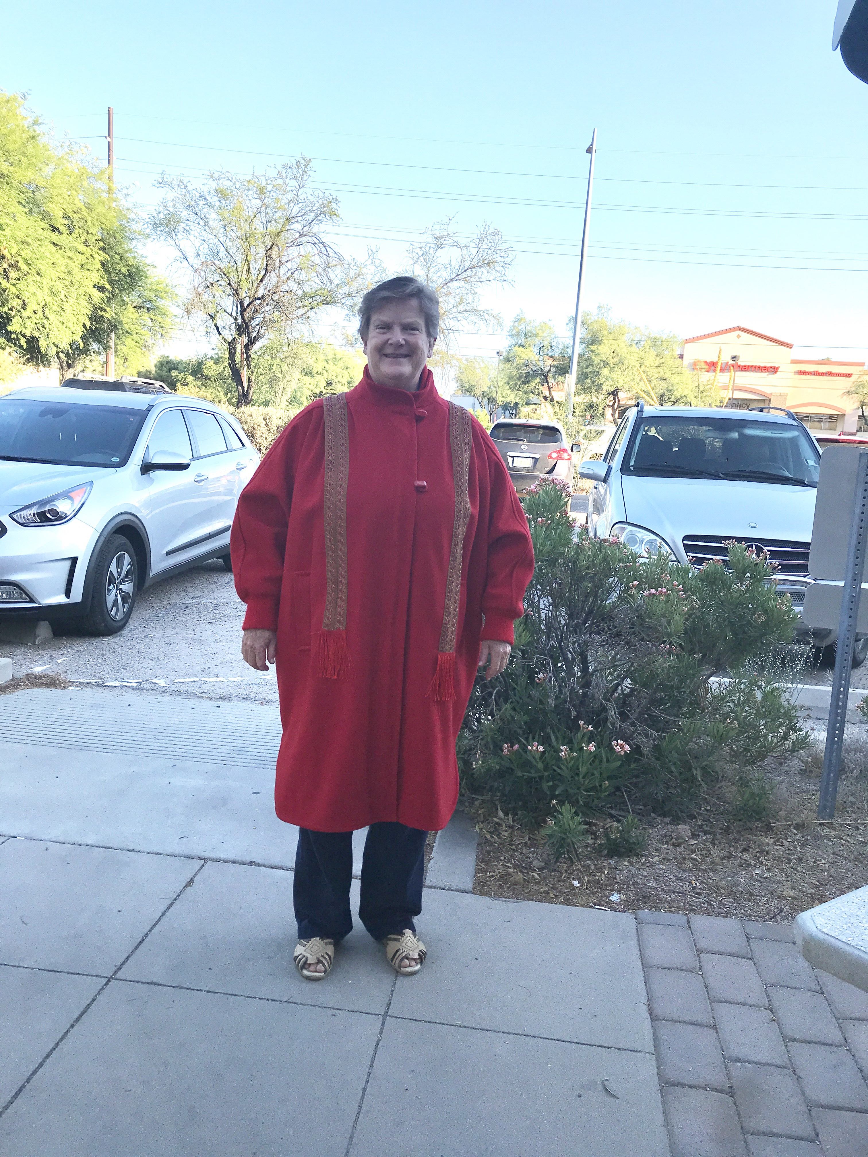 A woman stands in a parking lot wearing a long red woolen coat