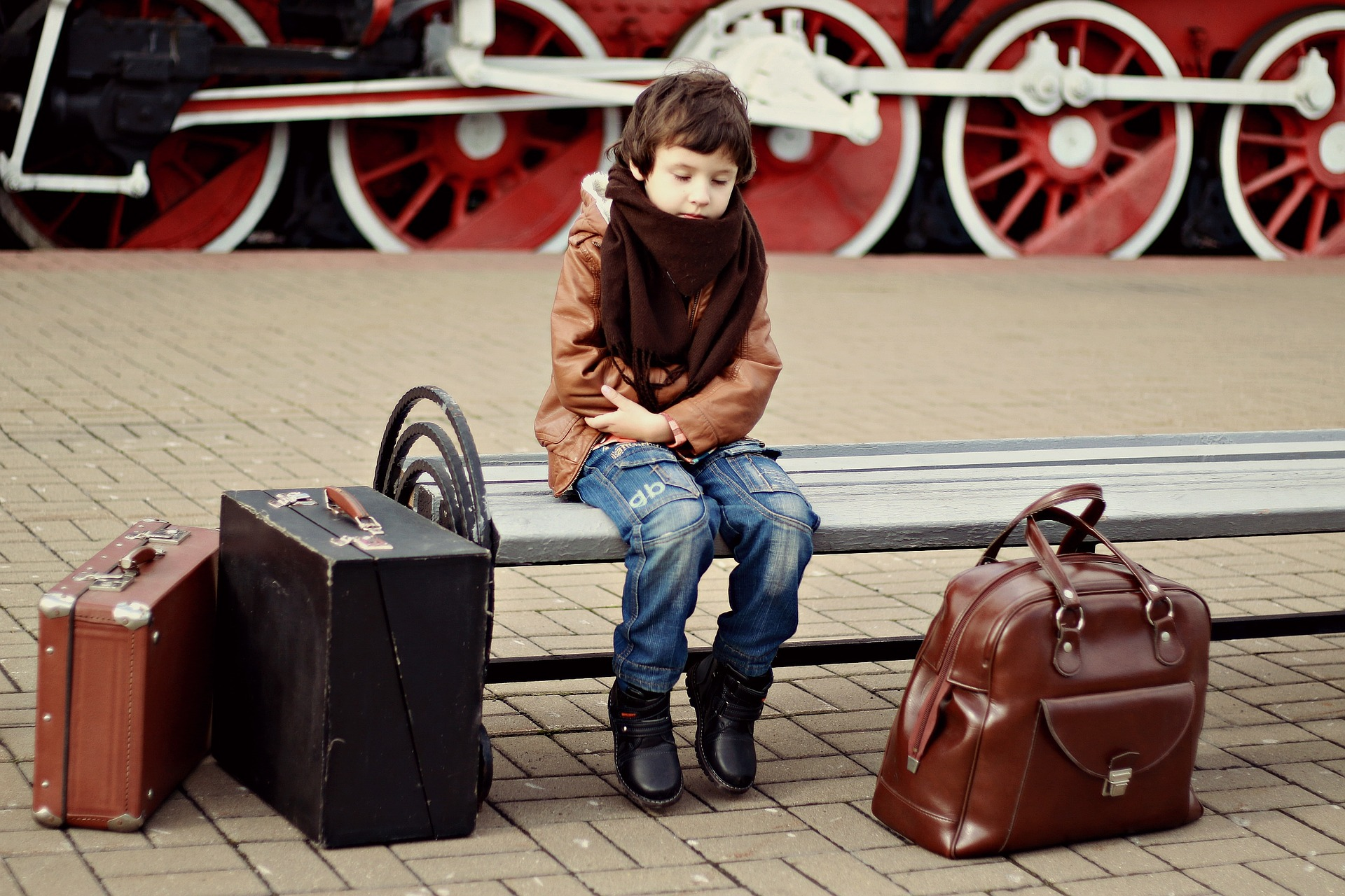 young child on train station bench near suitcases