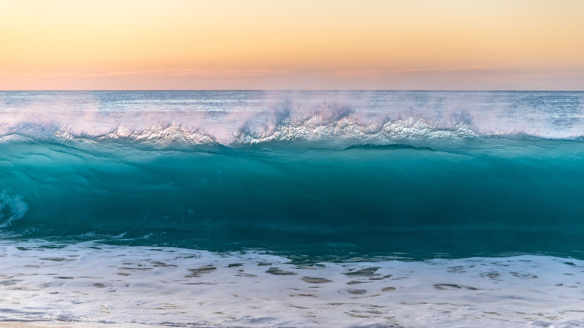 turquoise and white ocean waves against an orange sunset
