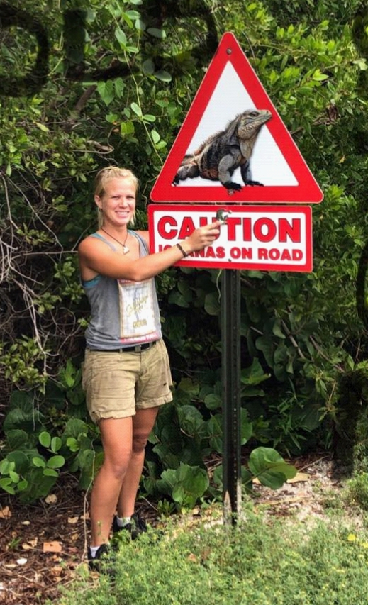 a woman stands by a caution sign for iguanas in the road