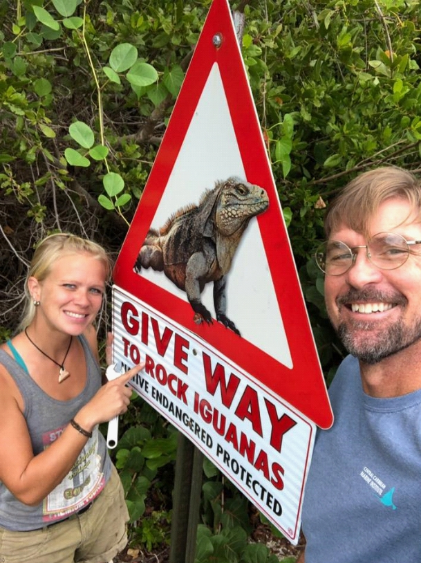 A woman and man stand near a Give Way to Iguanas sign