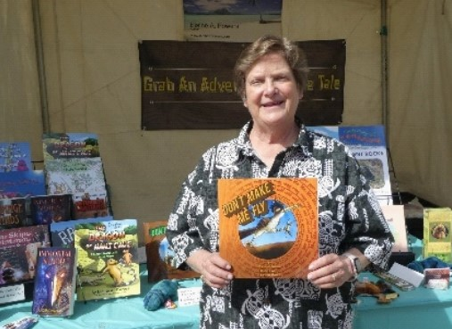 author Elaine A Powers holds a book in front of her booth at Tucson Festival of Books