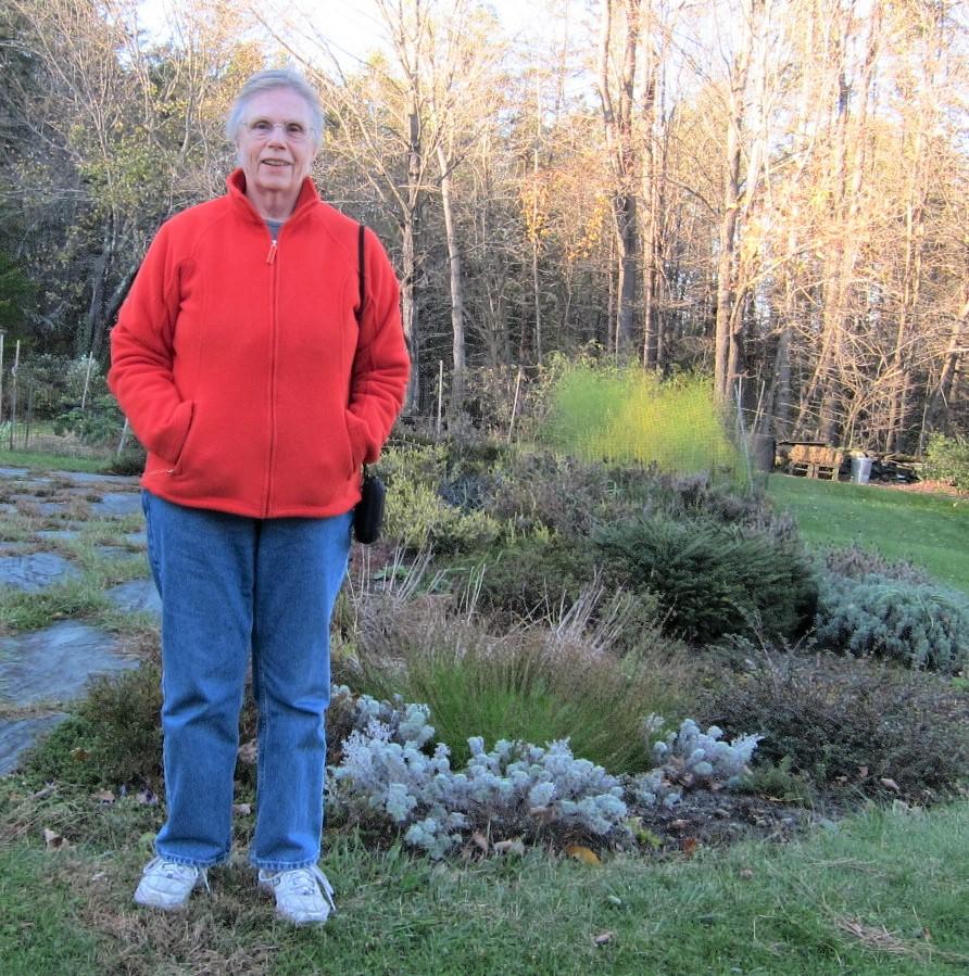 Author Jo Busha standing in her garden
